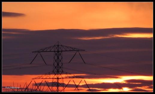 Hoog gespannen hangt de draad,de mast draagt de draad met spanning .De zonsondergang is rood van kleur het kleurt de lucht roder als dat de mast is