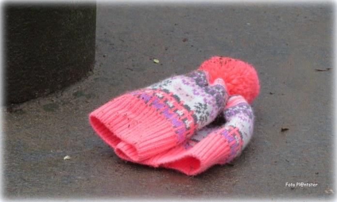 Een meisje heeft haar muts niet meer op... het lag nu op de grond