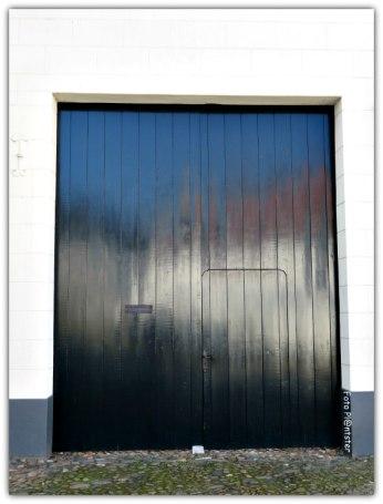 In de hoogglanzende deur een witte gloed van de huizen, die aan de overkant van de straat staan.