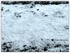 Een korrelige witte aanblik van de gevallen hagel op de grond.